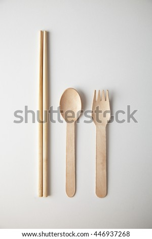 Kitchen utencils set for takeaway business: wooden recycling eco spoon, fork and chopsticks isolated on white top view - stock photo