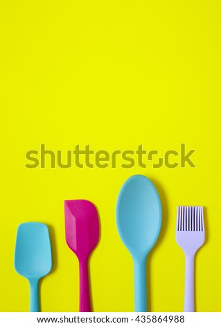 Kitchen utensils - a blue silicone cooking spoon, pink baking spatula and purple pastry brush on a yellow background forming a page border - stock photo