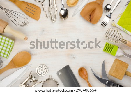 Kitchen utensils and cutlery background with copy space in center - stock photo
