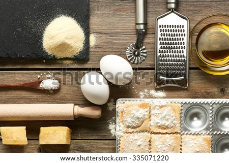 Kitchen utensils and ingredients for homemade pasta ravioli on wooden table - stock photo
