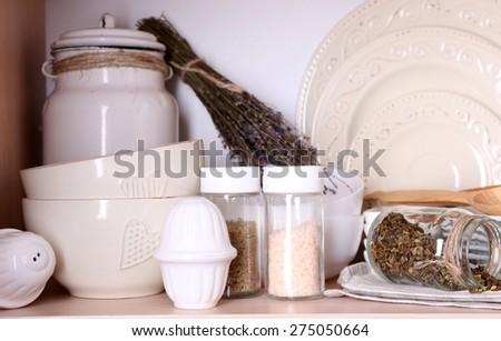 Kitchen utensils and tableware on shelf - stock photo