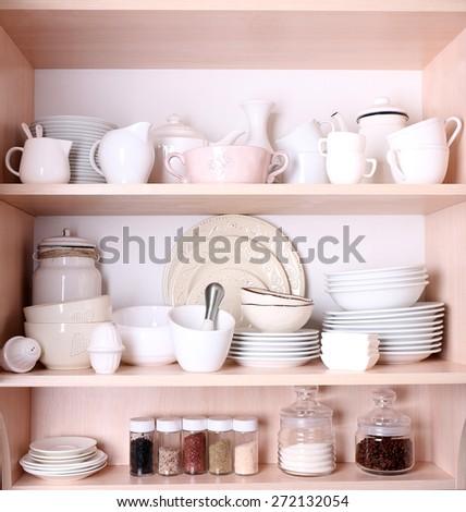 Kitchen utensils and tableware on shelves - stock photo