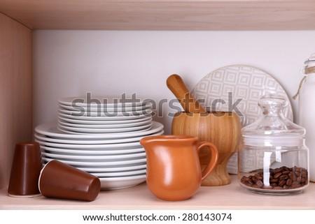 Kitchen utensils and tableware on wooden shelf - stock photo