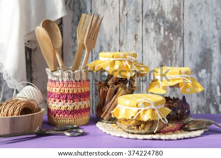 Kitchen utensils. Cinnamon, Cloves and Turmeric  in a glass jars on the wooden rustic background - stock photo
