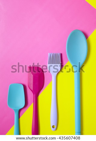 Kitchen utensils - Cooking spoons, spatulas and a pastry brush on a colorful pink and yellow background, forming a page border - stock photo