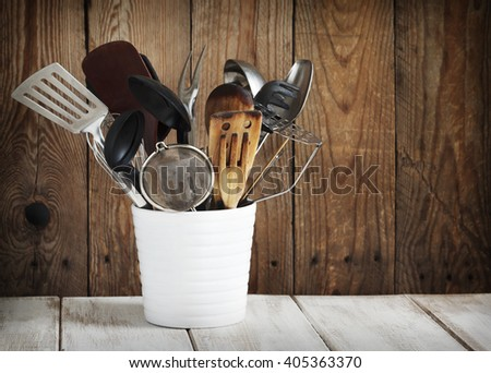 Kitchen utensils in a ceramic container on a wooden wall background - stock photo