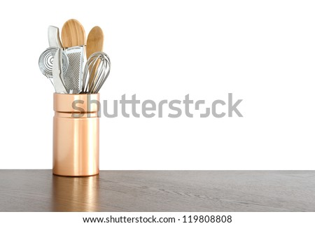 Kitchen utensils in a ceramic container on white background - stock photo