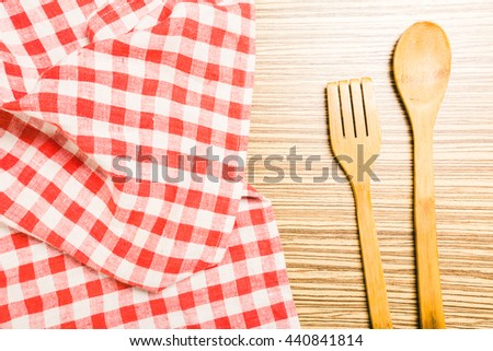 Kitchen utensils on tablecloth on wooden table over - stock photo