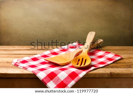 Kitchen utensils on tablecloth on wooden table over grunge background - stock photo