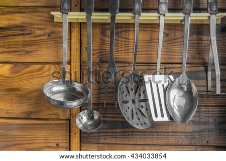 kitchen utensils on the wall on a wooden background - stock photo