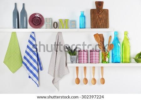 Kitchen utensils on wooden shelves, close up - stock photo