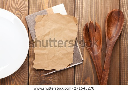 Kitchen utensils over wooden table background with paper for copy space   - stock photo