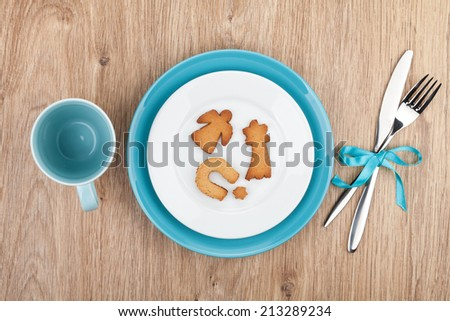 Kitchen utensils over wooden table with cookies on plate - stock photo