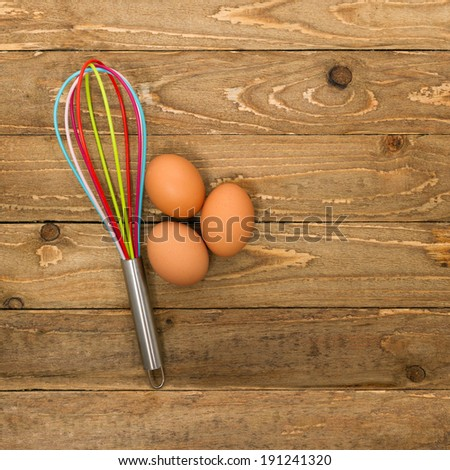 Kitchen whisk and eggs on a vintage wooden background - stock photo