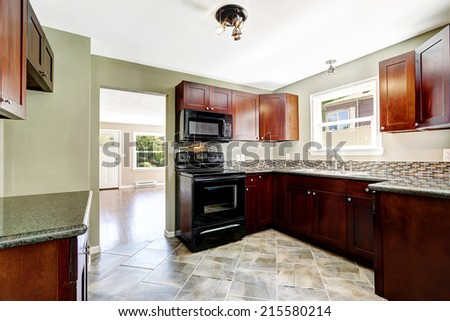 Kitchen with bright burgundy cabinets and black appliances. Light mint walls and tile floor - stock photo