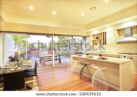 Kitchen with expensive dining table and green garden, ceramic plates and flower vases have on the white wooden table, chairs made with metal sticks, gas cooker and oven, shiny floor with wood designs.