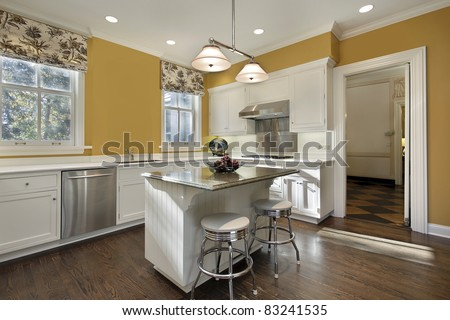 Kitchen with gold walls and white cabinetry - stock photo