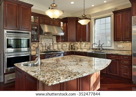 Kitchen with granite island and cherry wood cabinetry - stock photo