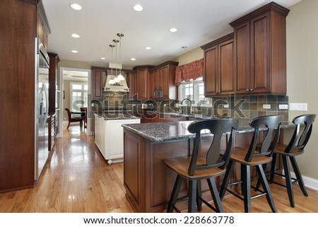 Kitchen with island and dark tile backsplash - stock photo