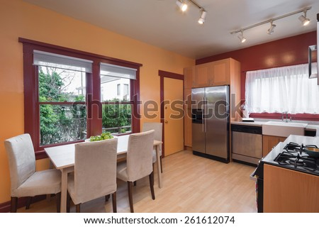 Kitchen with light wooden cabinets, view window, breakfast table and chairs with dark red, mustard wall paint.  - stock photo