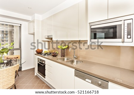 Kitchen with luxurious tools and white walls, luxury living room including glass table also chairs, oven and gas cooker have attached to the pantry cupboard, ceramics with fruits near the cookers.