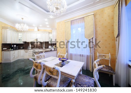 Kitchen with luxury furniture in classic style, marble floor and small dining table. - stock photo