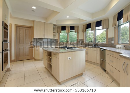 Kitchen with stove-top island and oak wood cabinetry.