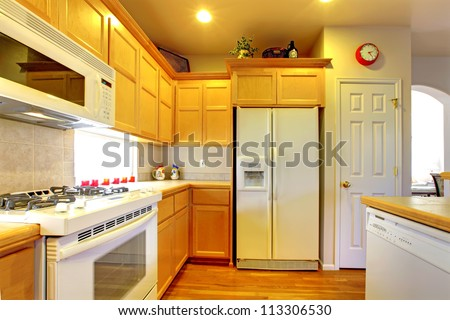 Kitchen with yellow wood cabinets and white appliances and hardwood floors. - stock photo