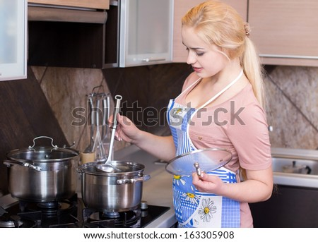 Kitchen Woman. Beautiful happy smiling woman in kitchen interior cooking in pot - stock photo