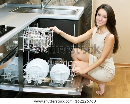 Kitchen Woman. Girl in the kitchen using dishwasher. view of young woman in kitchen doing housework - stock photo