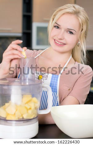 Kitchen Woman. Young woman preparing fruits for the blender