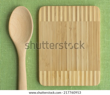Kitchen wooden cutting board with wooden spoon on a linen green tablecloth. Still life of isolated of objects