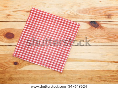 Kitchen. Wooden kitchen table with empty red tablecloth for dinner. View from above with copy space - stock photo