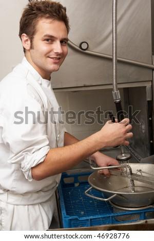 Kitchen Worker Washing Up In Restaurant Kitchen - stock photo