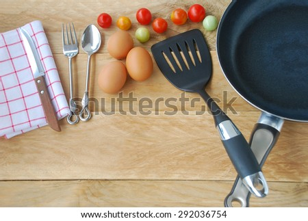 kitchenware are including frying pan, flipper used in frying, spoon, fork, knife, napkins, eggs and fresh tomatoes, placed on a wooden background in top view. - stock photo