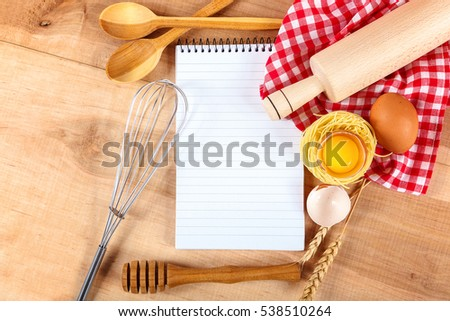 Kitchenware, egg and a prescription notepad on wooden.