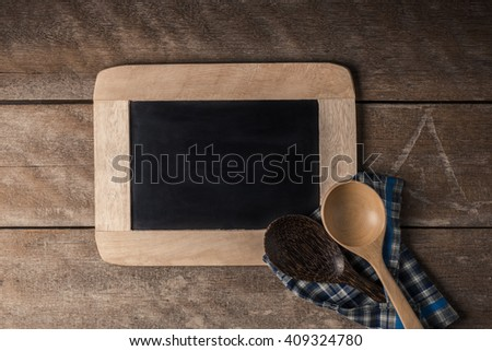 Kitchenware on a blackboard with a blue checkered napkin on wooden table - stock photo
