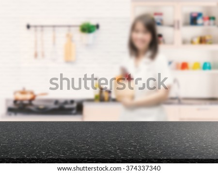 kitchenware on black counter with kitchen blurred background - stock photo