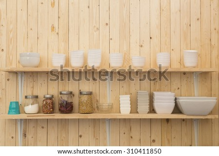 Kitchenware on wooden shelves - stock photo