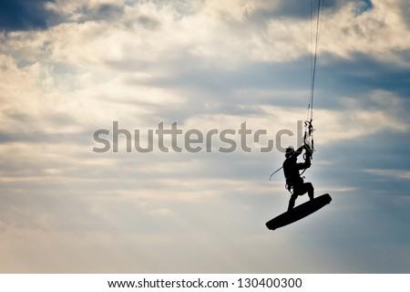 KITE BOARDING. Kite surfer flying up high. - stock photo
