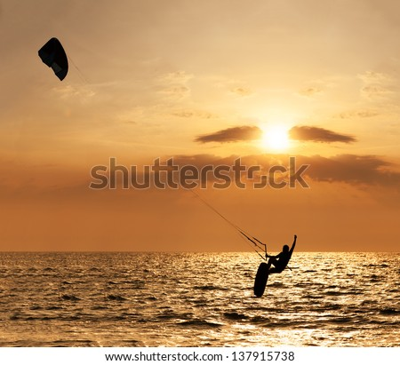 Kite surfer jumping from the water at sunset ocean  - stock photo