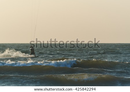 Kite-surfer jumping on the sea waves - stock photo