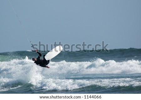 Kite surfer ( kite boarder ) jumping the waves near Cayucos, California - stock photo