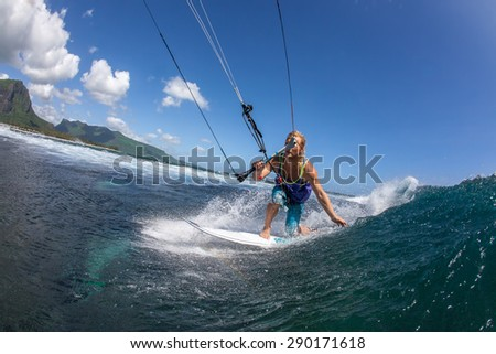 Kite surfer rides among the huge tubes and waves of the Indian Ocean on the island of Mauritius