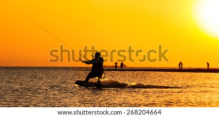 Kite surfing on the background of orange sunset in the sea - stock photo