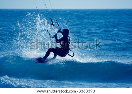 kite surfing, silhouette of sportsmen on blue - stock photo
