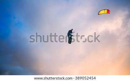 Kiteboarder performing a jump against sky at sunset