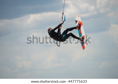 Kiteboarding.   A kite surfer jumping on sky background