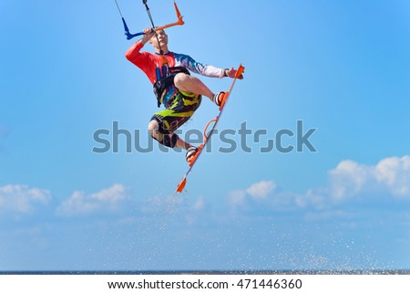 Kiteboarding.  A kite surfer rides the waves