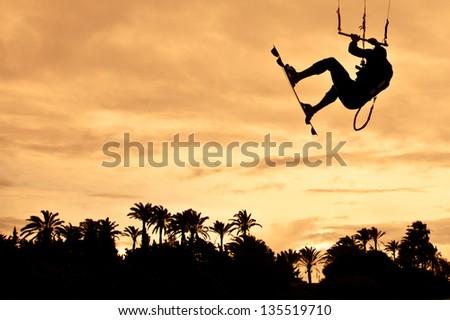 Kiteboarding. High jump at sunset. - stock photo